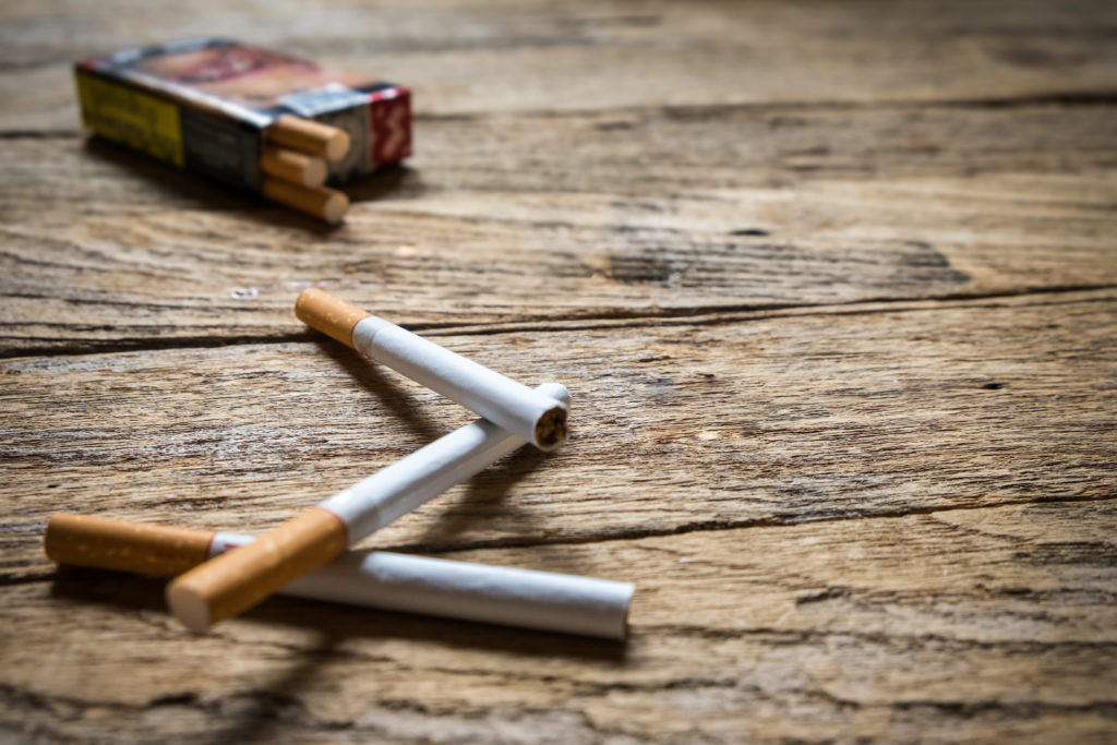 Tobacco in the cigarette, lying on a wooden table